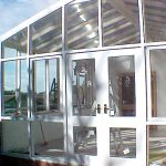 White awnings and glass walls installation on glasshouse / conservatory
