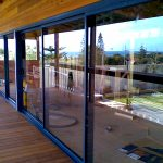 Blue awnings and glass doors on wooden structure