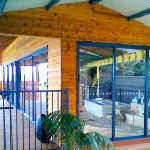 Wood walls with sliding glass doors and blue awnings